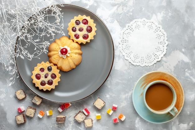 Vista superior de pequeños pasteles dentro de la placa gris con café con leche en la mesa de luz pastel galleta café azúcar dulce
