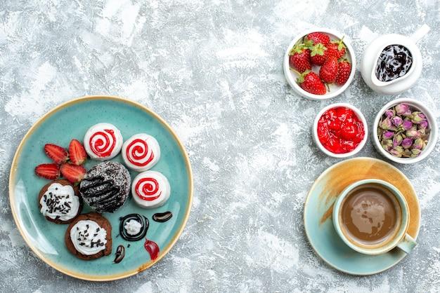 Vista superior de pequeños pasteles dulces con frutas y una taza de café sobre un fondo blanco pastel de galletas de galletas dulces pastel de azúcar