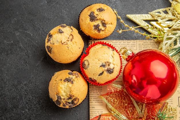 Vista superior de pequeños pasteles dulces con juguetes de árbol de navidad sobre fondo gris