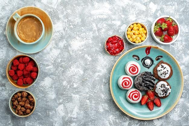 Vista superior de pequeños pasteles dulces con taza de café y caramelos sobre un fondo blanco pastel de tarta galleta dulce galleta de azúcar
