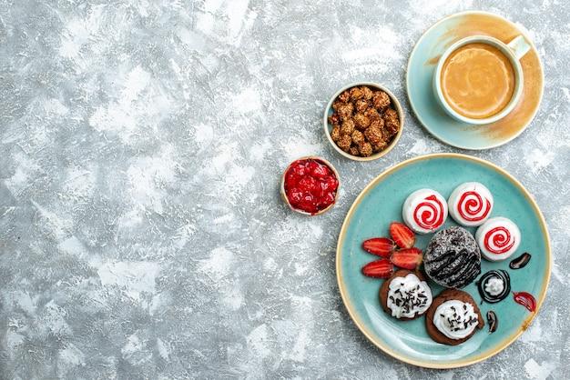 Vista superior de pequeños pasteles dulces con una taza de café sobre fondo blanco pastel de galletas dulces azúcar café cooki