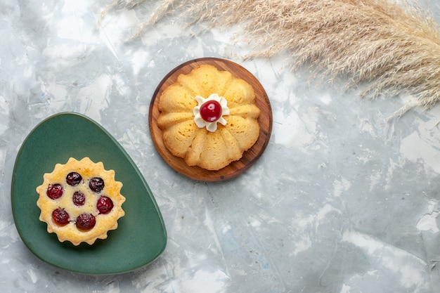 Vista superior de pequeños pasteles con frutas en la mesa de luz pastel galleta dulce color azúcar