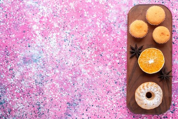 Vista superior de pequeños pasteles con rodaja de naranja en la superficie rosa