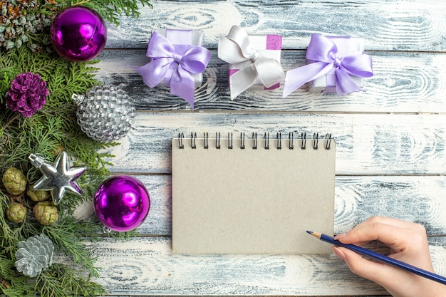 Vista superior pequeños regalos árbol de navidad juguetes ramas de abeto cuaderno lápiz en mano femenina sobre fondo de madera