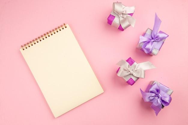 Vista superior de pequeños regalos con bloc de notas en la superficie rosa