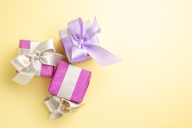 Vista superior de pequeños regalos en superficie de color amarillo claro.