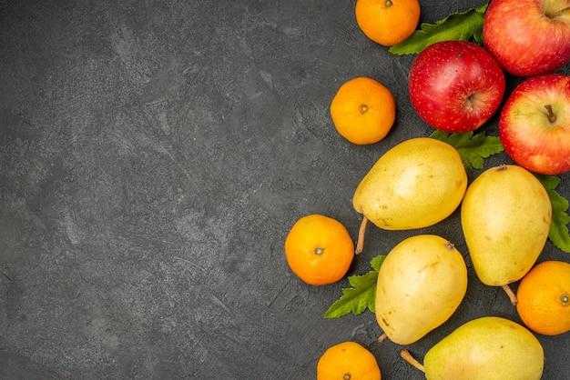 Vista superior de peras dulces frescas con mandarinas y manzanas sobre fondo gris
