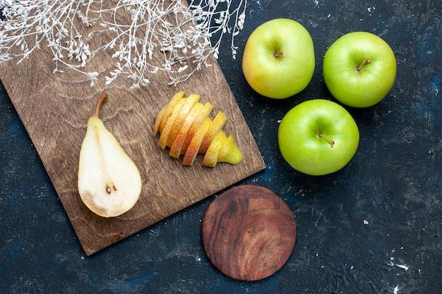 Vista superior de peras frescas enteras en rodajas y dulces con manzanas verdes en el escritorio azul oscuro, salud alimentaria suave de frutas