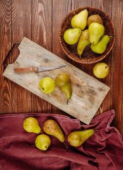 Vista superior de peras maduras frescas en una cesta de mimbre y en una tabla de cortar sobre un fondo de madera