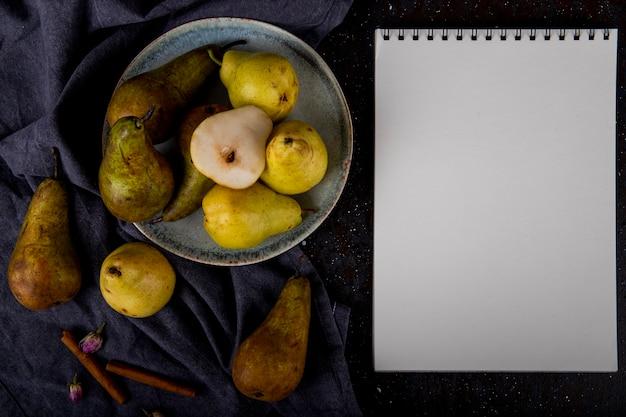 Vista superior de peras maduras frescas en un plato de cerámica con cuaderno de dibujo sobre fondo negro con espacio de copia