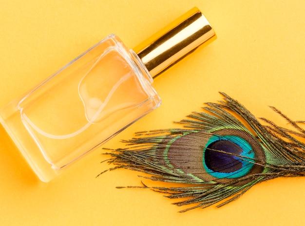 Vista superior de perfume orgánico con pluma de pavo real