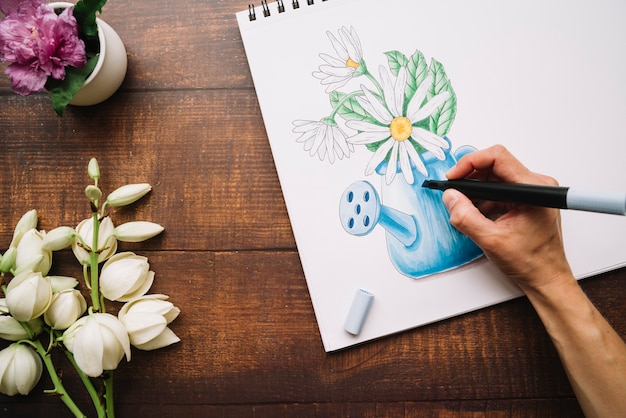 Vista superior de una persona dibujando un jarrón de flores sobre lienzo con un marcador negro en la mesa de madera