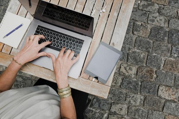 Vista superior de la persona escribiendo en la computadora portátil al aire libre