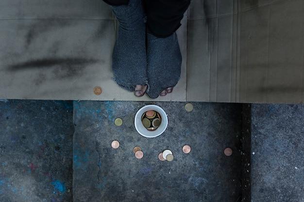 Vista superior persona sin hogar con agujeros en sus calcetines