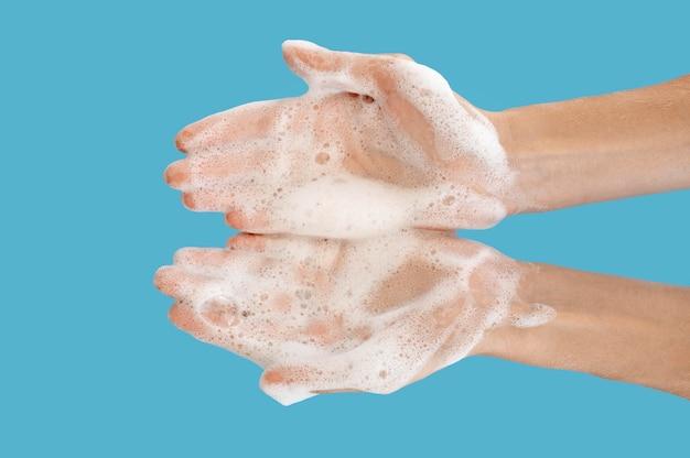 Vista superior persona lavándose las manos con fondo azul.