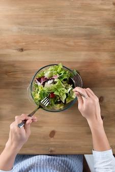 Vista superior de la persona que prepara una ensalada saludable en un tazón