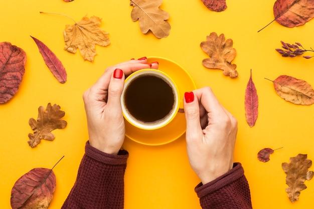 Vista superior de la persona que sostiene la taza de café con hojas de otoño