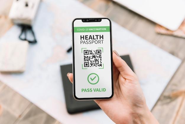 Vista superior de la persona que tiene un pasaporte de salud virtual en un teléfono inteligente
