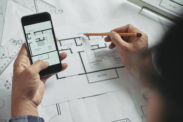 Vista superior de una persona recortada irreconocible que compara planos en papel y digitales
