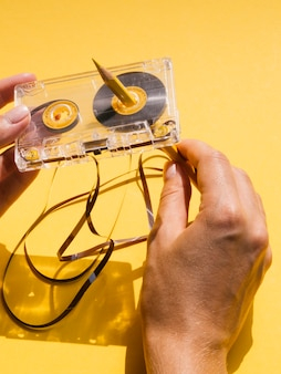 Vista superior persona reparando cinta de cassette con lápiz