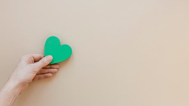 Vista superior persona sosteniendo un corazón verde sobre fondo beige