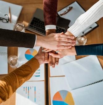 Vista superior de personas juntando las manos de acuerdo durante la reunión