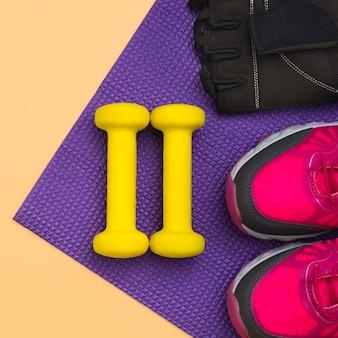 Vista superior de pesas con guantes de gimnasia y zapatillas de deporte