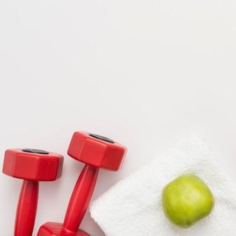 Vista superior de pesas con toalla y manzana