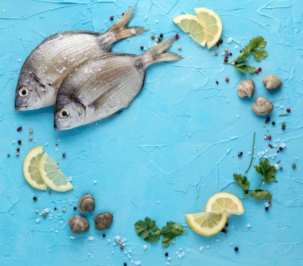 Vista superior de pescado con almejas y rodajas de limón.