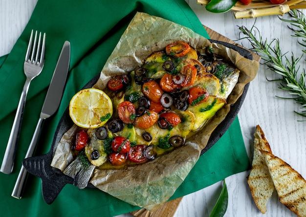 Vista superior de pescado asado cubierto con papa, tomate cherry, oliva y limón.
