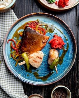 Vista superior de pescado asado con verduras rodajas de jengibre en escabeche y salsa de soja en un plato rústico