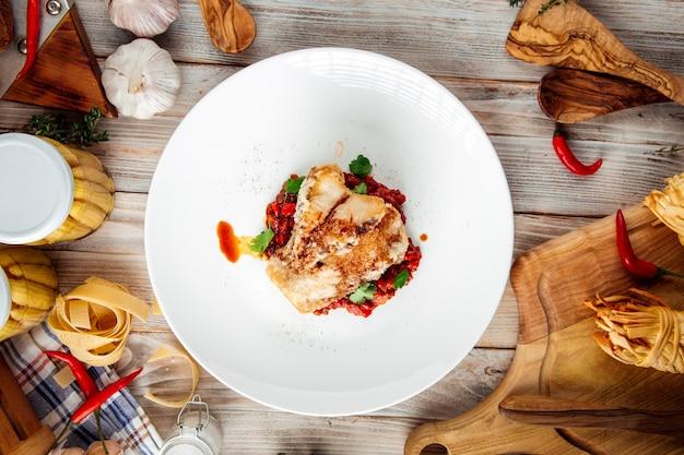 Vista superior de pescado blanco frito con guiso de verduras en salsa roja sobre la mesa de madera