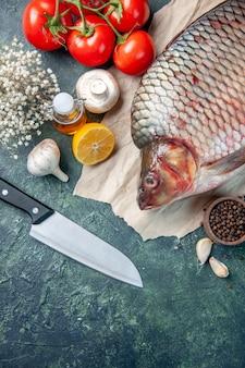 Vista superior de pescado crudo fresco con tomates rojos y champiñones sobre fondo azul oscuro