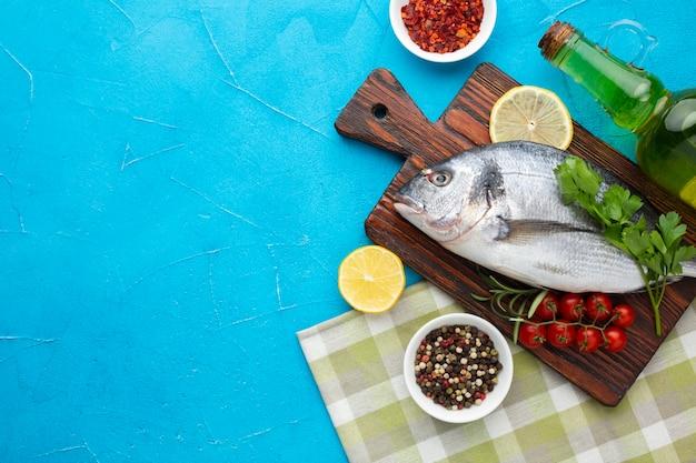 Vista superior de pescado fresco con condimentos en la mesa