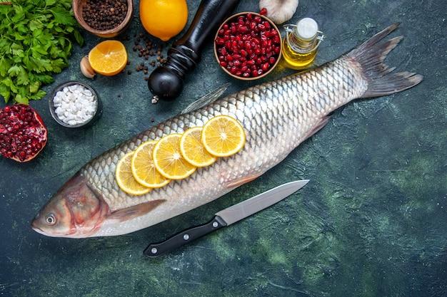 Vista superior de pescado fresco con cuchillo de rodajas de limón en la mesa de la cocina