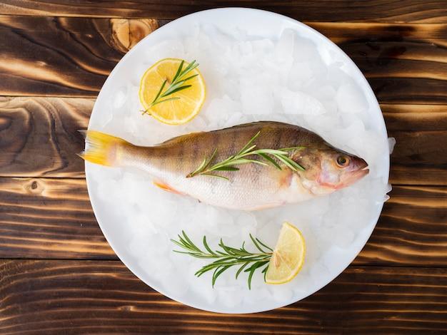 Vista superior de pescado fresco en un plato con hierbas