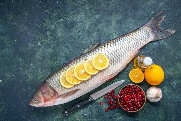 Vista superior de pescado fresco con rodajas de limón, cuchillo, semillas de granada, tazón de fuente en la mesa de la cocina con lugar para copiar