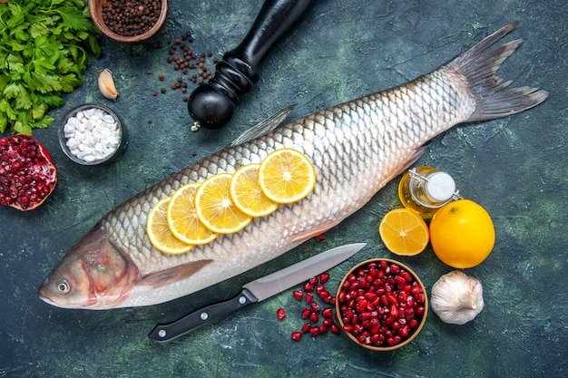 Vista superior de pescado fresco con rodajas de limón, cuchillo, semillas de granada, tazón de fuente en la mesa de la cocina