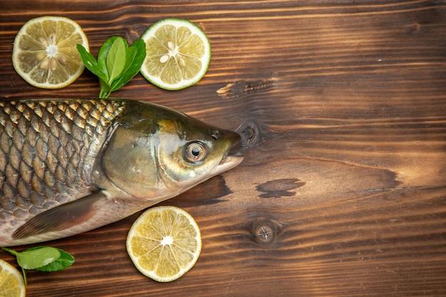 Vista superior de pescado fresco con rodajas de limón en el escritorio de madera