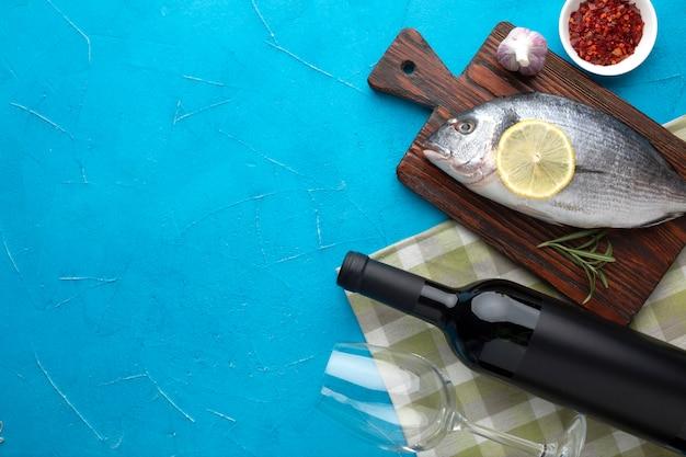 Vista superior de pescado fresco sobre fondo de madera con vino