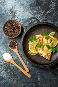 Vista superior de pescado frito en sartén con especias de limón y perejil en cucharas de madera pimienta negra en un tazón sobre fondo gris