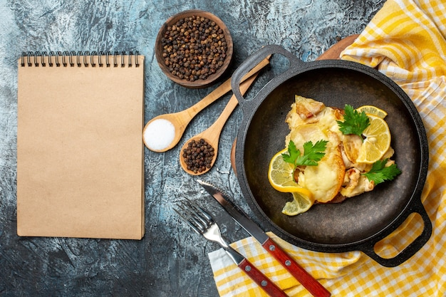 Vista superior de pescado frito en una sartén con especias de limón y perejil en un tazón y cucharas de madera, tenedor y cuchillo cuaderno sobre fondo gris