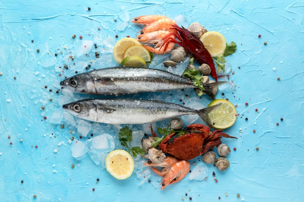 Vista superior de pescado con hielo y cangrejo.
