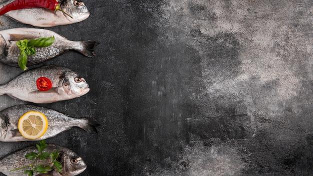 Vista superior de pescado en un lado con ingredientes.
