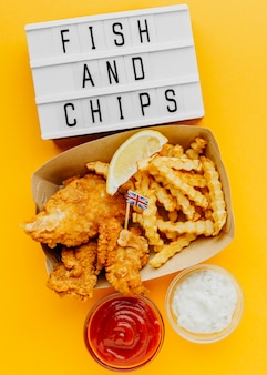 Vista superior de pescado y patatas fritas con caja de luz y salsa
