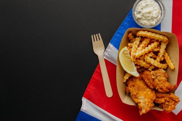 Vista superior de pescado y patatas fritas con espacio de copia y bandera de gran bretaña