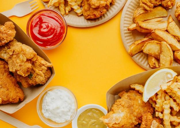 Vista superior de pescado y patatas fritas con espacio de copia y salsas