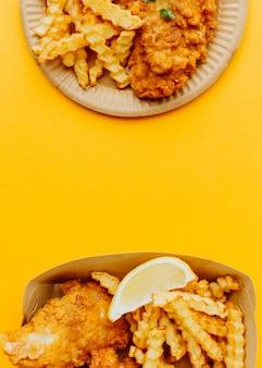 Vista superior de pescado y patatas fritas con espacio de copia