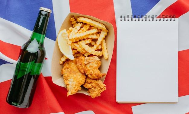 Vista superior de pescado y patatas fritas en un plato con un cuaderno y una botella de cerveza