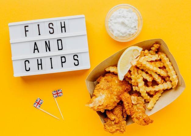Vista superior de pescado y patatas fritas con salsa y caja de luz